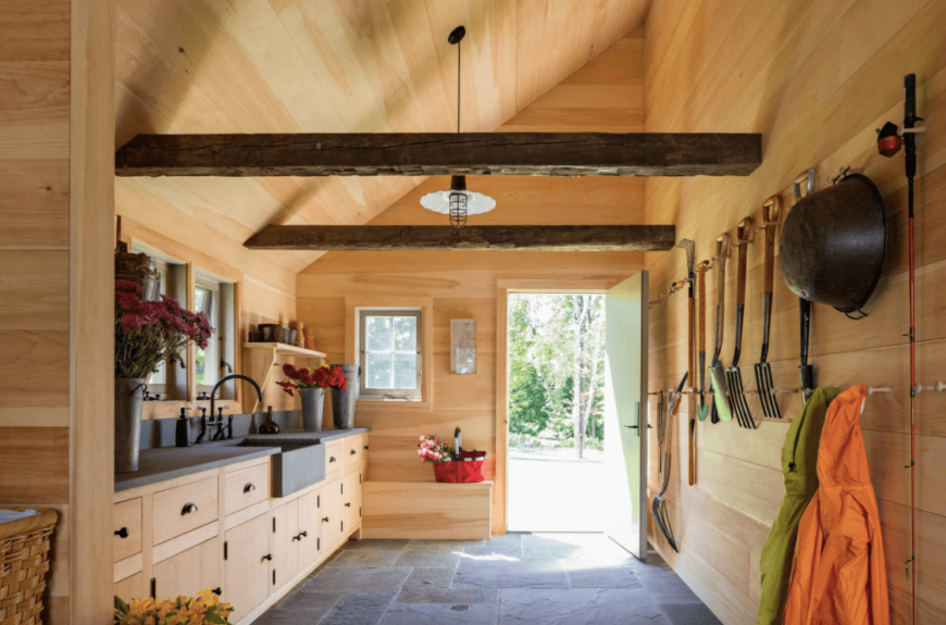 This kitchen boasts wooden walls and ceiling with exposed beams. The flooring looks amazing together with the kitchen's style.