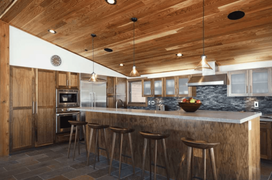 A rustic kitchen setup with a stylish center island lighted by pendant lights hanging from the wooden shed ceiling.