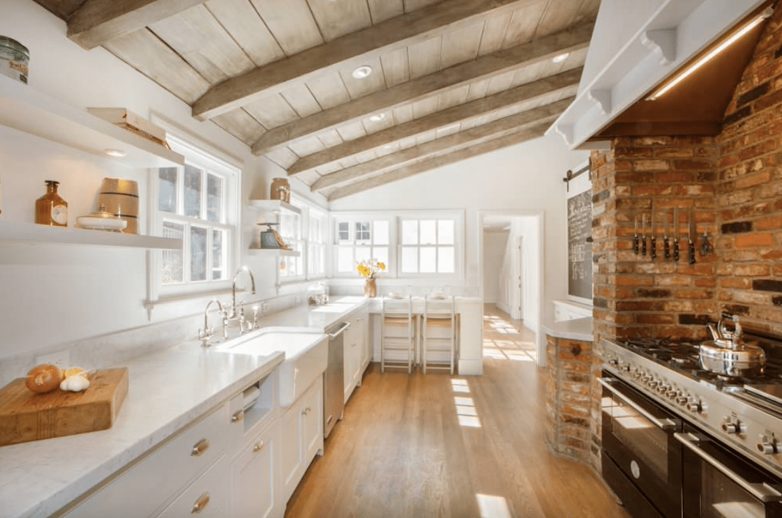 This kitchen boasts brick walls, a rustic shed ceiling with beams and white kitchen counters with marble countertops.