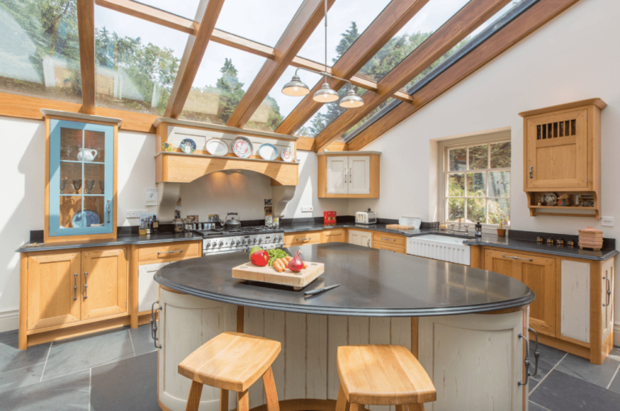 Large kitchen area featuring a stylish center island and a stunning glass shed ceiling with exposed beams.