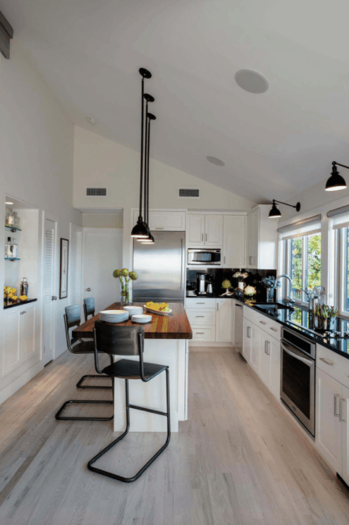 Medium-sized kitchen featuring a modish center island and breakfast bar stools lighted by stylish black pendant lights hanging from the shed ceiling.