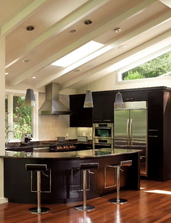 A modish kitchen featuring an elegant breakfast bar with cozy bar stools set on the hardwood flooring.