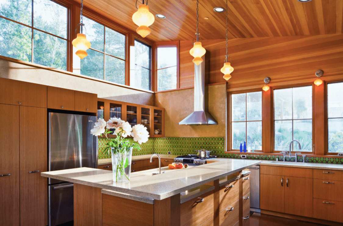 This kitchen is surrounded by cherry-finished walls and kitchen counters. The area is lighted by wall lights and pendant lights set on the shed ceiling.