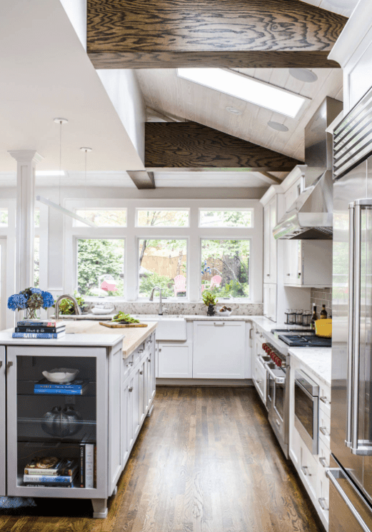 This kitchen features hardwood flooring and a stylish shed ceiling with a skylight.
