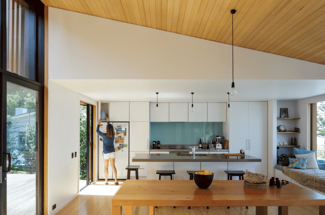 Dine-in kitchen boasting a large center island with a breakfast bar and a rectangle dining table set lighted by pendant bulb lights.