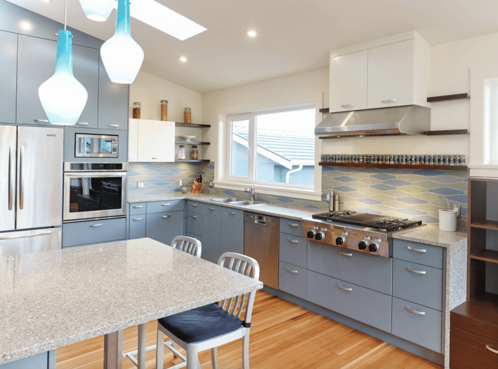 This kitchen features gray cabinetry and kitchen counters, along with hardwood flooring and a shed ceiling with pendant lights, recessed lights and a skylight.