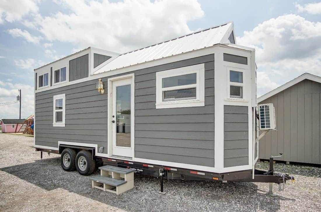 Exterior photo of a long tiny house with partial gabled roof and elevated loft area.