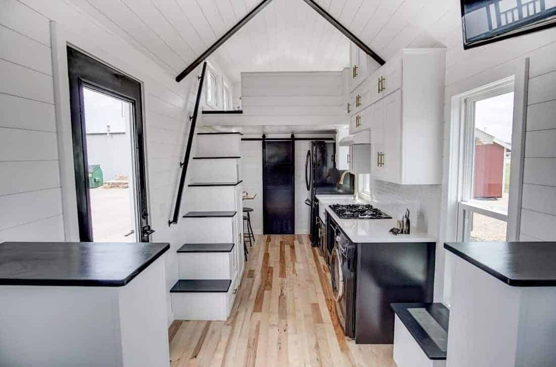 Interior photo of the kitchen and stairs in a custom built tiny house. White walls and ceiling look fantastic with the light natural wood flooring.