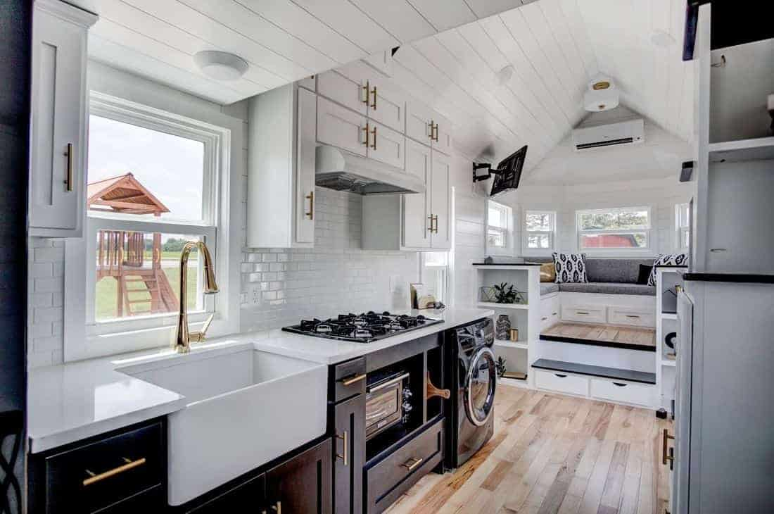 The fabulous kitchen in this tiny house includes a large farmhouse sink, range and oven - partially located under the loft sleeping area.
