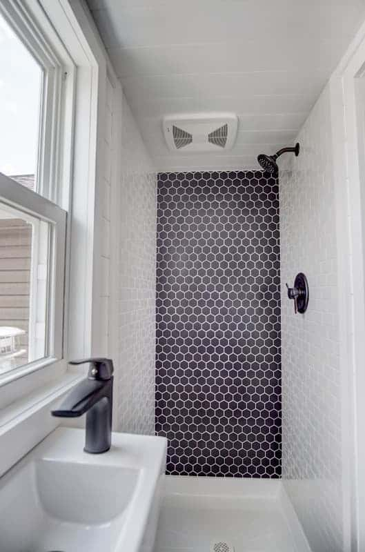 Walk-in shower in tiny home bathroom with black and white color scheme.