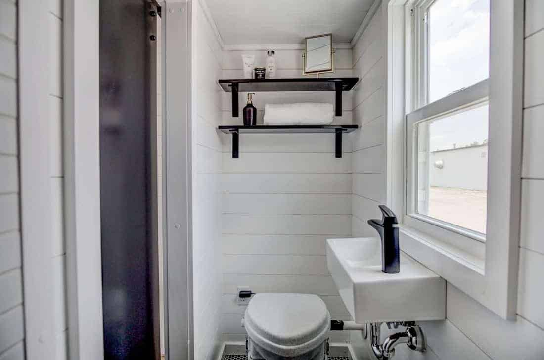 Stylish modern floating sink in white bathroom. Includes floating shelves above the toilet.