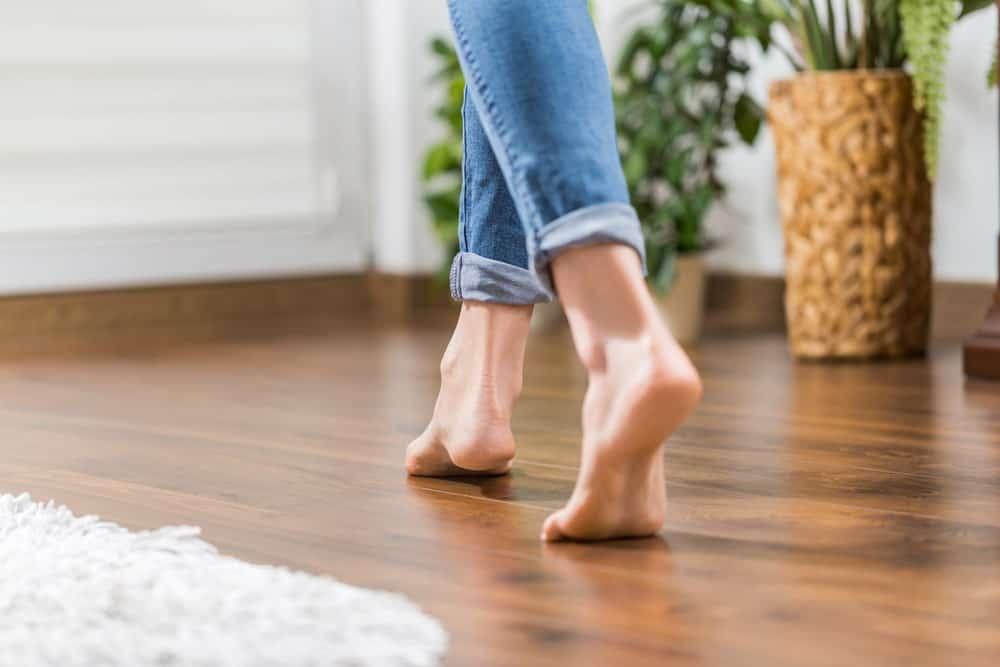 A close look at a woman walking on hardwood flooring.
