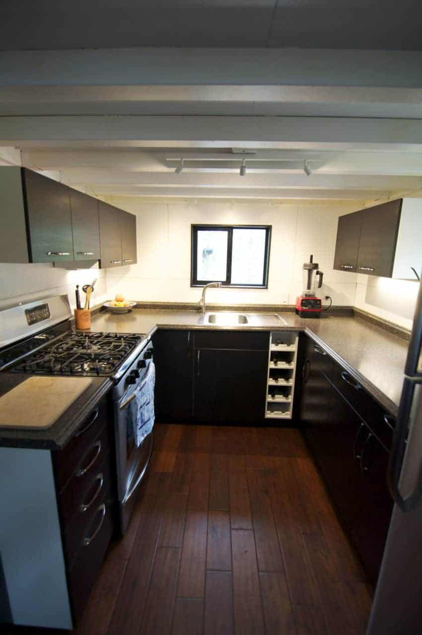 This is one of the biggest tiny house kitchens. It's a large u-shaped and is nearly as big as kitchens in regular homes. Yes, this is a tiny house on wheels - but they decided to allocate a decent amount of space to the kitchen. There's loads of counterspace to work on as well as a full oven and range.