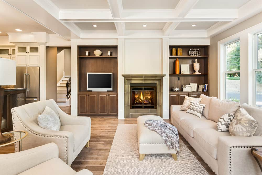 The bright white coffered ceiling of this living room connects with the white panel of the fireplace that is flanked by a couple of dark wooden bookshelves. These are a match for the light gray sofa set with a cushioned ottoman coffee table.