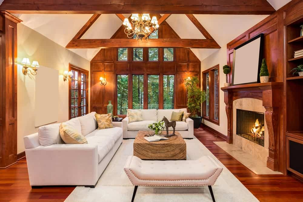 The triangular exposed ceiling beams of the cathedral ceiling matches well with the wooden mantle of the fireplace, hardwood flooring and the frames of the tall windows. These are contrasted by the light gray sofa set and complemented by the yellow lights of the chandelier and wall lamps.