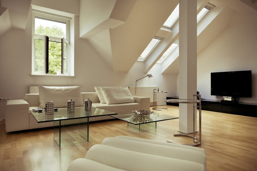This is simple living room with a touch of modern-style flair to its two coffee tables made entirely of glass. This goes well with the light hardwood flooring that is complemented by the light beige sofa, white walls and the low cathedral ceiling with skylights at the far corner