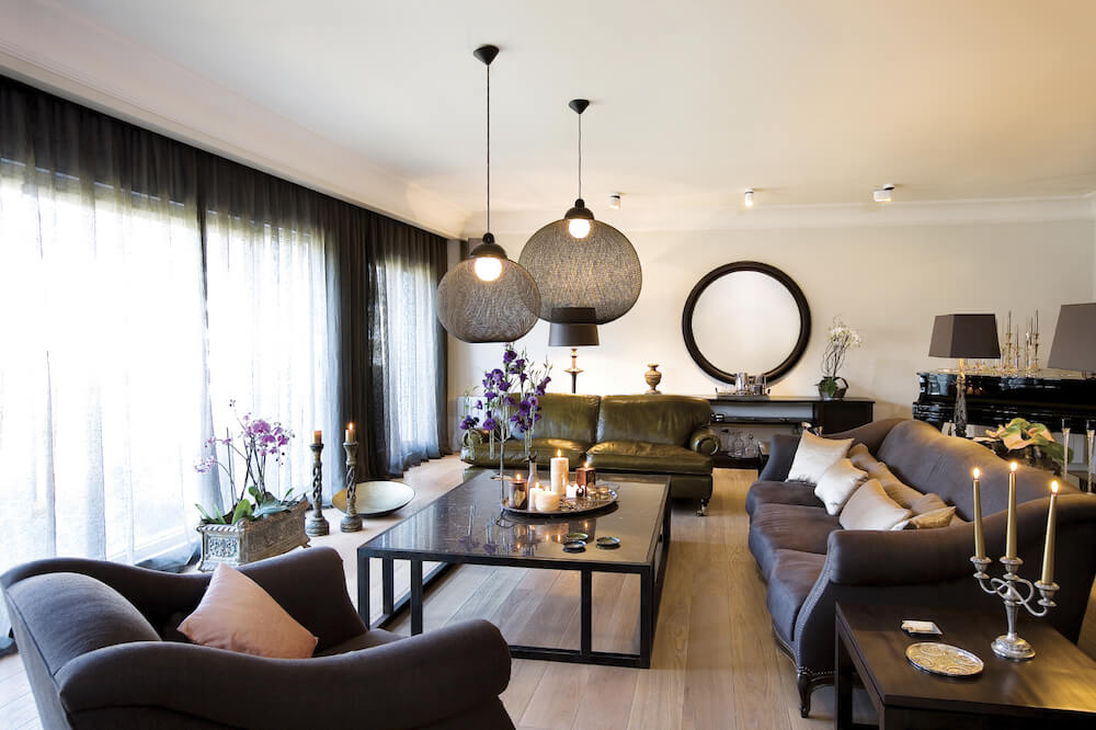 This is a gorgeous living room with a couple of pendant lights hanging over the sleek black coffee table. These pendant lights are covered by a spherical black woven material that filters lights. This matches quite well with the black sofa set.