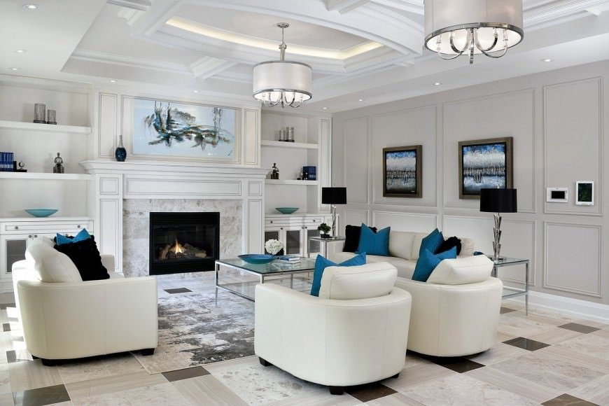 This is an elegant formal living room with white leather sofas and cushioned armchairs paired with contrasting black and blue pillows that go well with other accents of the room with a blue tone like the paintings on the light gray walls and the large one above the white mantle of the fireplace.