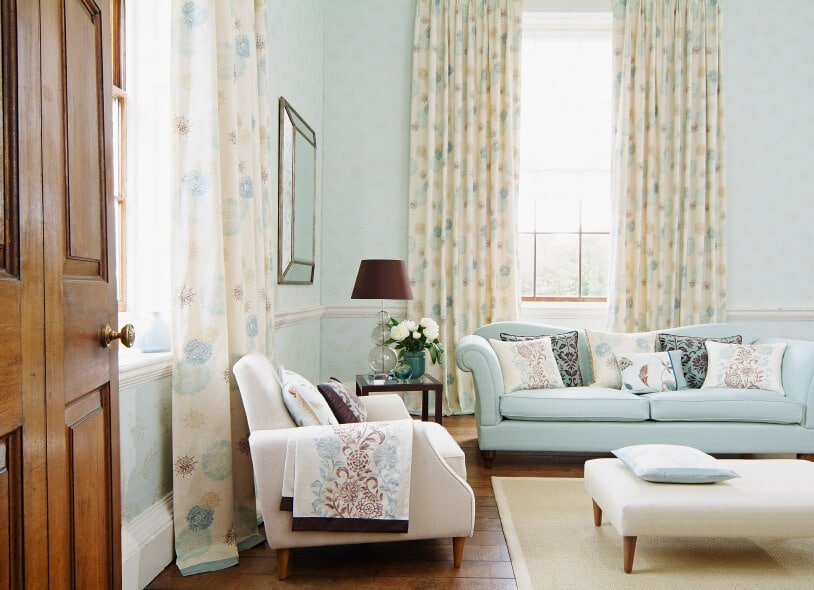 The beautiful shabby-chic light blue walls are complemented by the fabulous colorful beige curtains of the two bright windows. This also complements the light blue sofa that is paired with a beige cushioned armchair and a cushioned ottoman coffee table.