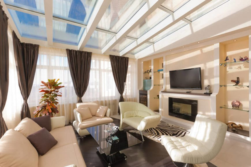 The bright ceiling of this living room is mostly made of skylights forming into a large glass ceiling with white frames in between. The natural lights coming in complement the light tones of the beige walls, pink sofa set and the matching light flooring tiles.