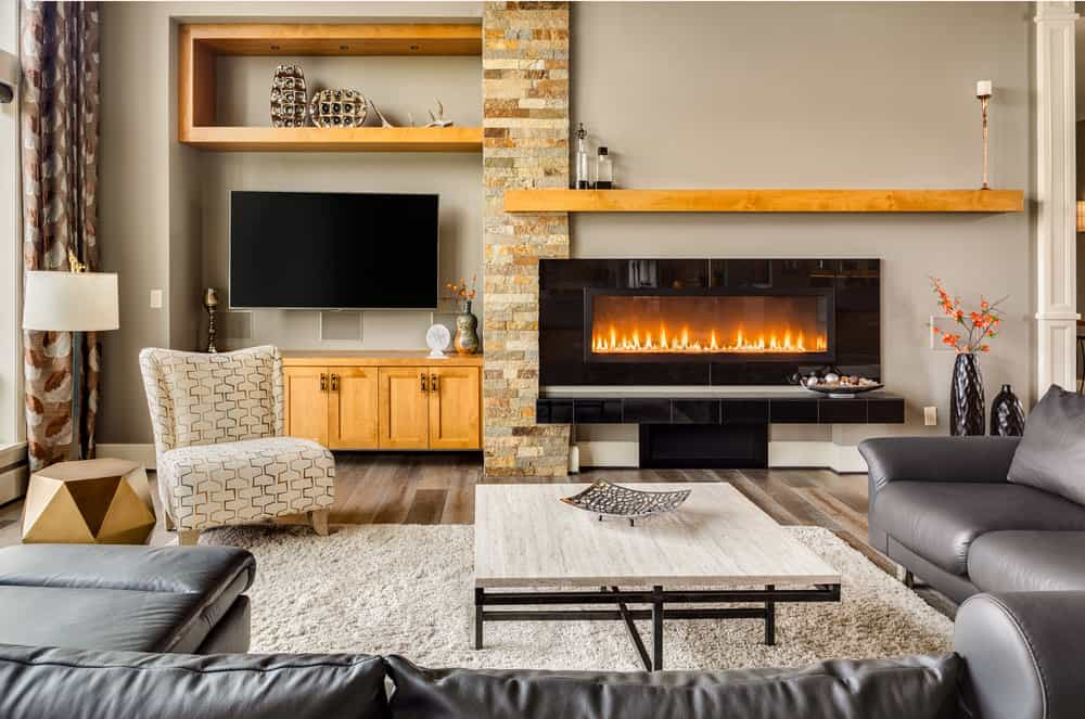 The modern fireplace of this living room is inlaid with shiny black tiles that stand out against the light gray walls topped with a wooden floating shelf. This is mirrored by the TV that is also topped with a floating shelf that has decors.