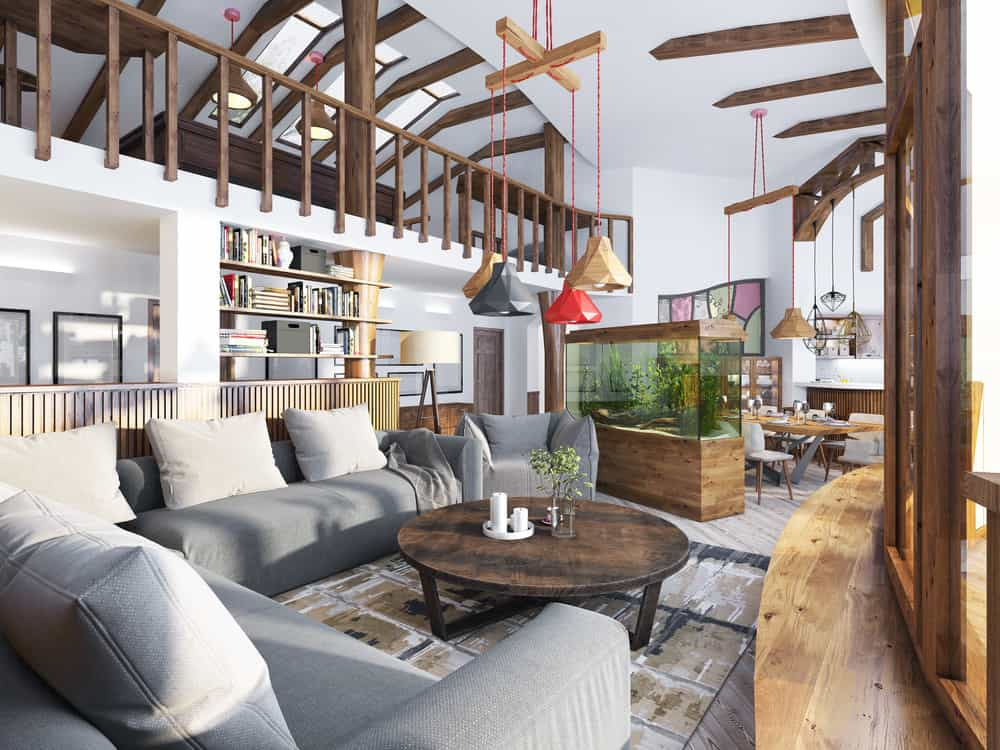 This comfortable and quirky living room has a large gray cushioned sectional sofa paired with a round wooden coffee table. This is then topped with a set of colorful pendant lights that hangs from the tall white cove ceiling brightened by natural lights.