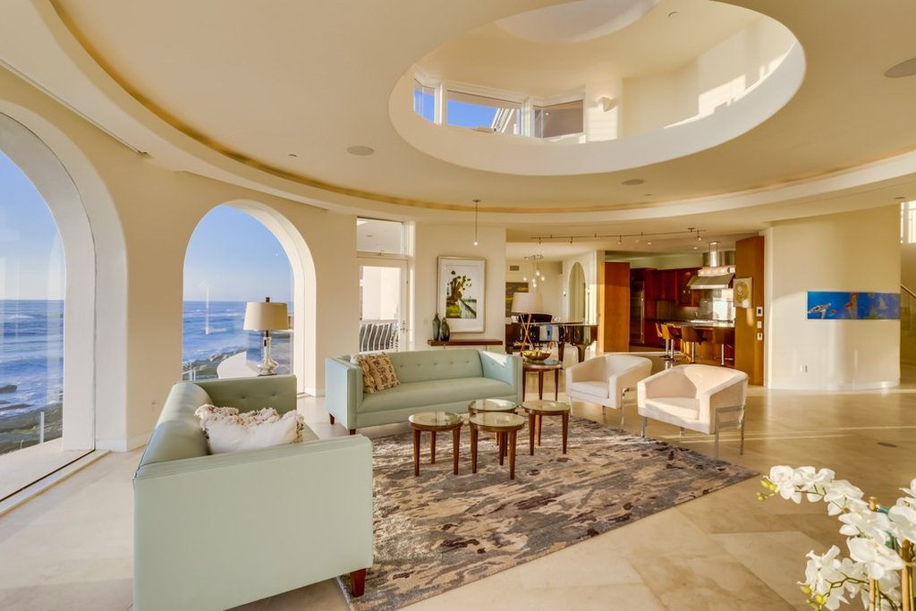 This mansion living room has a brilliant indoor balcony with a large circular part of the ceiling open to the next level. The beige ceiling matches with the beige walls that have arched glass windows and the beige marble flooring complemented by the light green sofas.