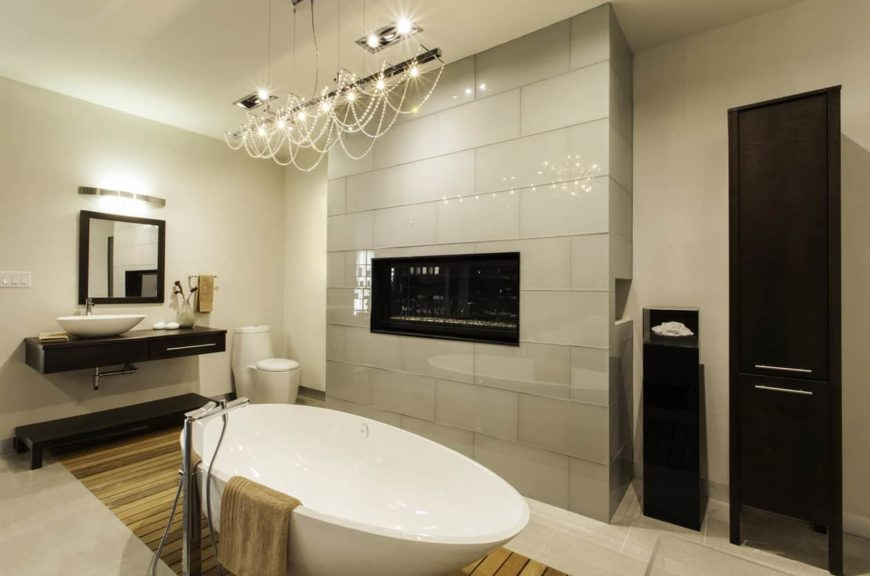A primary bathroom that offers a freestanding tub lighted by a gorgeous ceiling lighting and a floating vanity with a vessel sink, along with a fireplace.