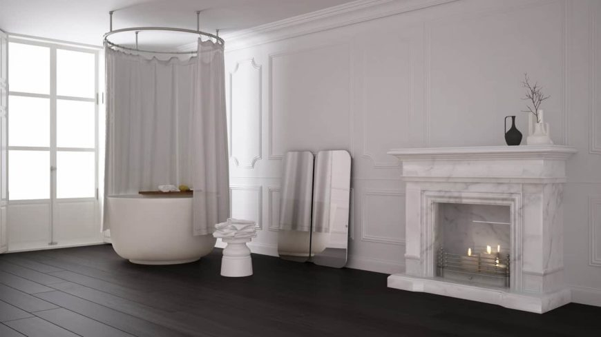 Spacious primary bathroom featuring white walls, dark hardwood flooring and a fireplace made of marble.