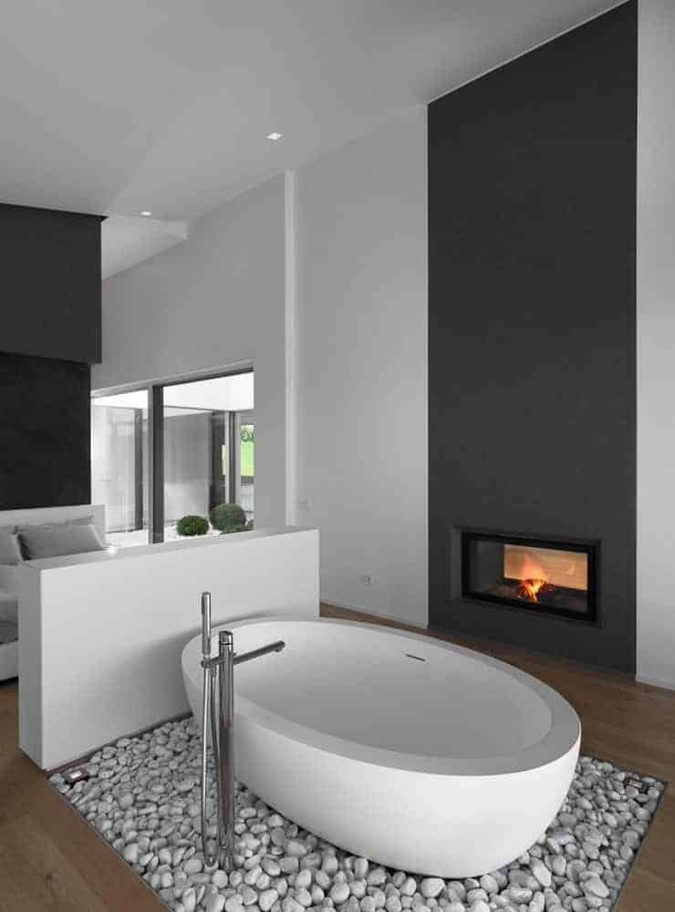Primary bathroom with a freestanding tub set on the stones and has a fireplace on its side.