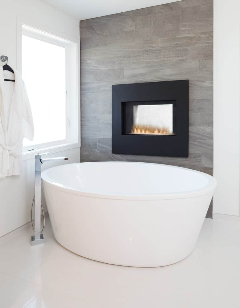 A focused shot at this primary bathroom's large freestanding tub with a fireplace on the wall.
