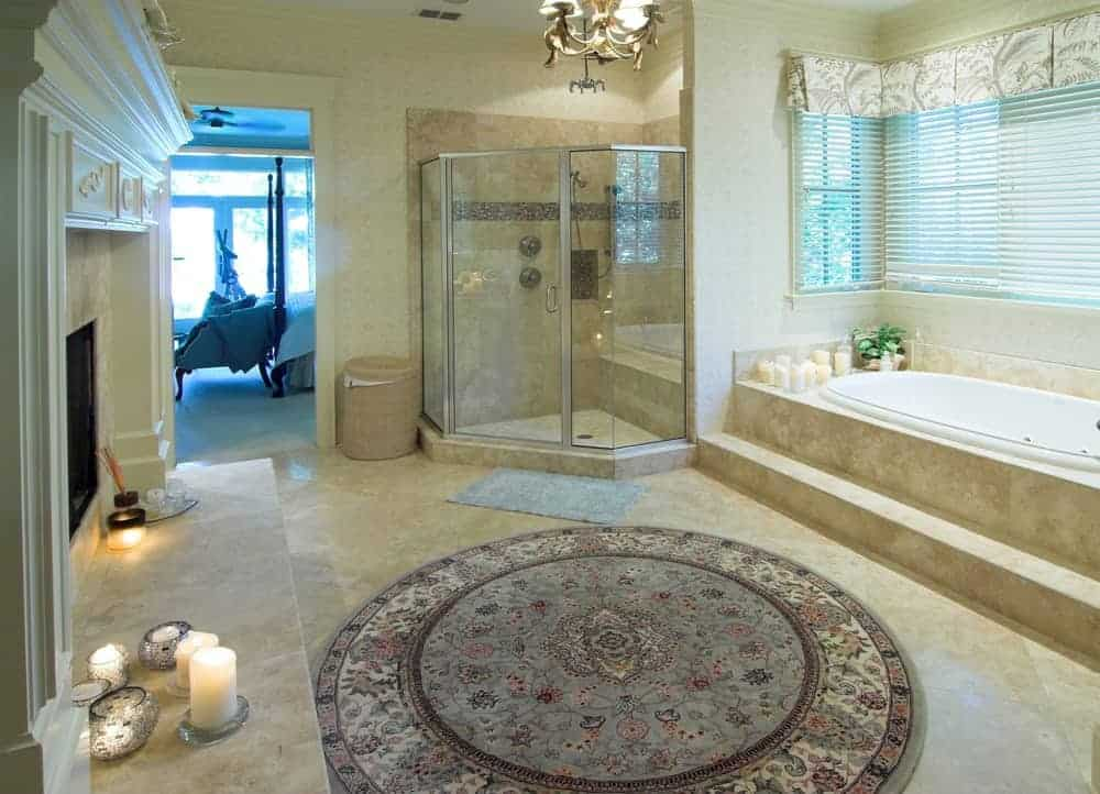 Spacious primary bathroom featuring classy tiles flooring topped by a circular rug. The room offers a walk-in shower, a drop-in tub and a fireplace.