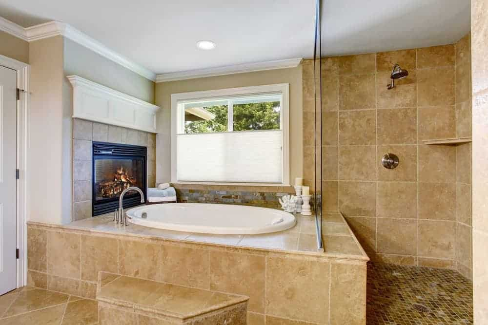 Primary bathroom featuring a deep soaking tub with a fireplace and an open shower room with tiles walls and floors.