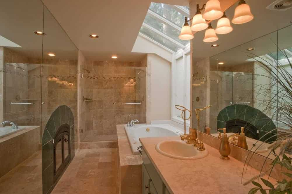 Primary bathroom with beige tiles walls and floors, and a large bathtub, along with a walk-in shower room.