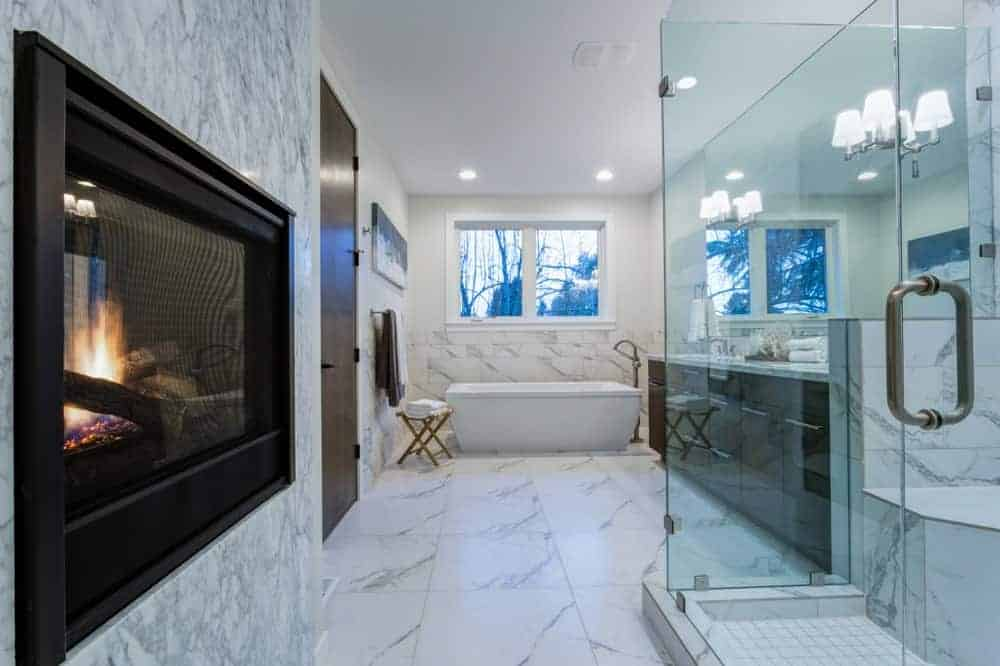 Large primary bathroom with marble tiles flooring. The room offers a freestanding tub and a walk-in shower room with a fireplace on the side.