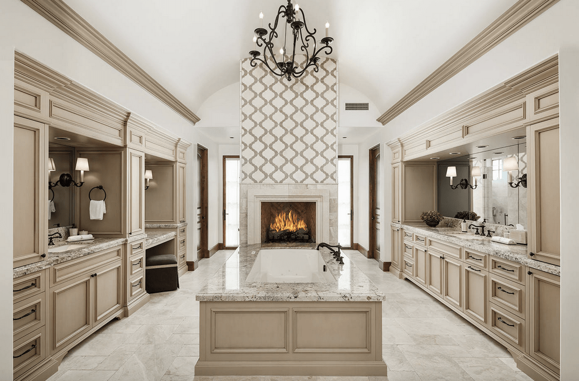 Large primary bathroom with marble tiles flooring and marble countertop on the sink counters. The fireplace looks brilliant, as well as the tall ceiling lighted by an elegant chandelier.