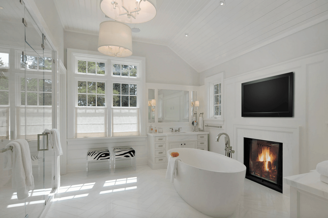 White primary bathroom with a walk-in shower room, a freestanding tub with a fireplace on the side and a large TV on top of the wall.