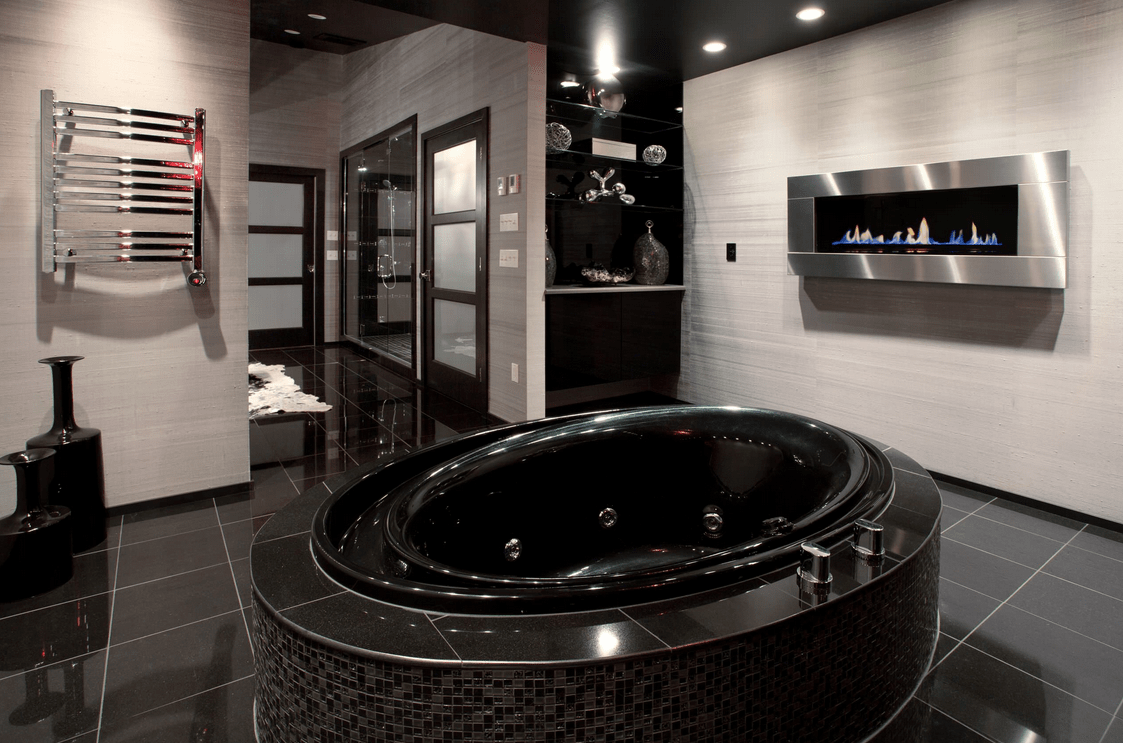 Contemporary primary bathroom featuring black tiles flooring and a stylish black soaking tub, along with a modern gas fireplace on the side.
