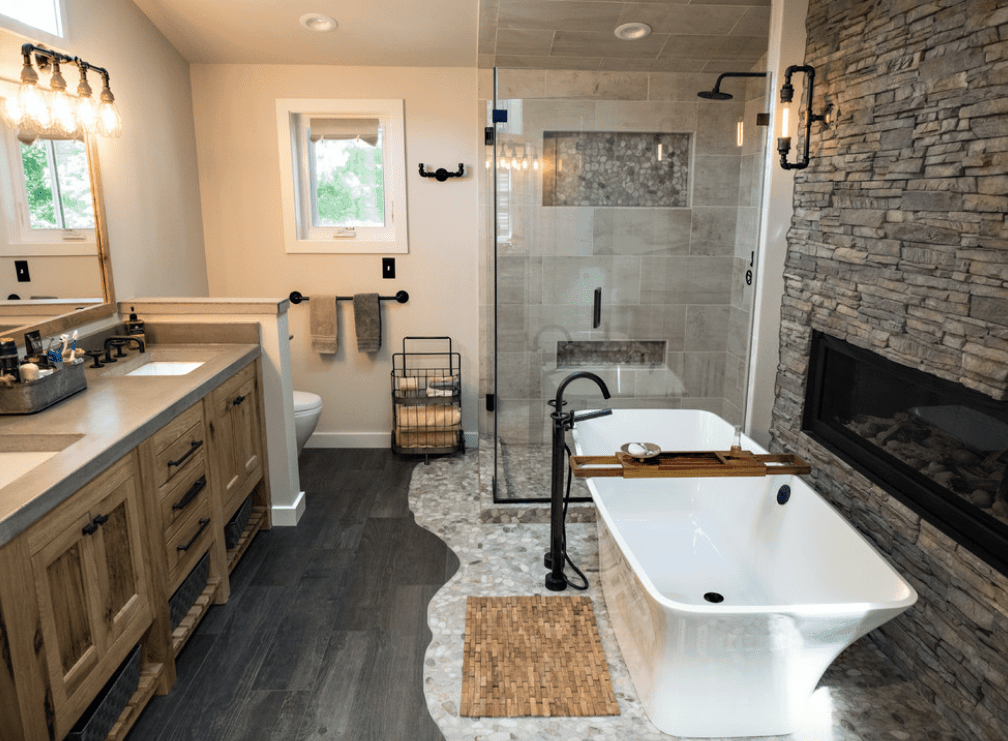Primary bathroom with a rustic double sink counter and dark hardwood flooring, along with a freestanding tub next to the fireplace and a corner walk-in shower.