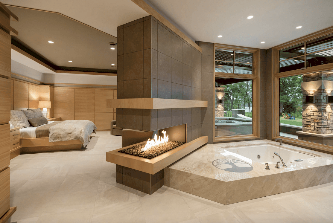 Large primary bedroom featuring its own bathroom with a deep soaking tub near the fireplace.