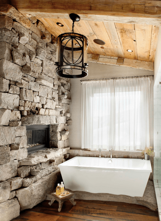 Primary bathroom with a stone wall and a fireplace, along with a white bathtub set on the hardwood flooring.