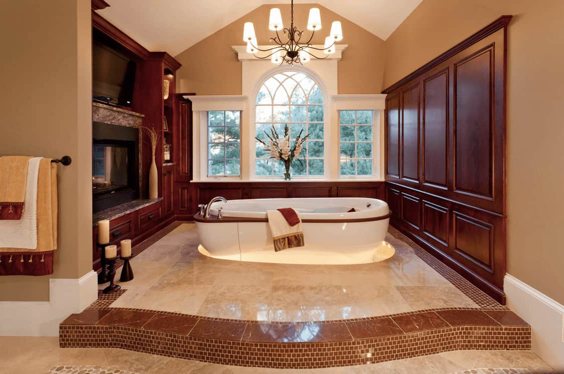 Primary bathroom with an elegant bathtub lighted by a fabulous chandelier set on the room's tall ceiling.