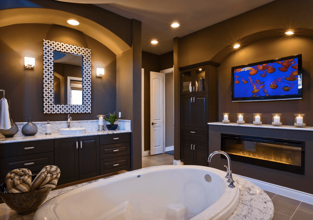 This primary bathroom boasts gray walls lighted by warm white lights. The room also offers a deep soaking tub on the middle and a fireplace.