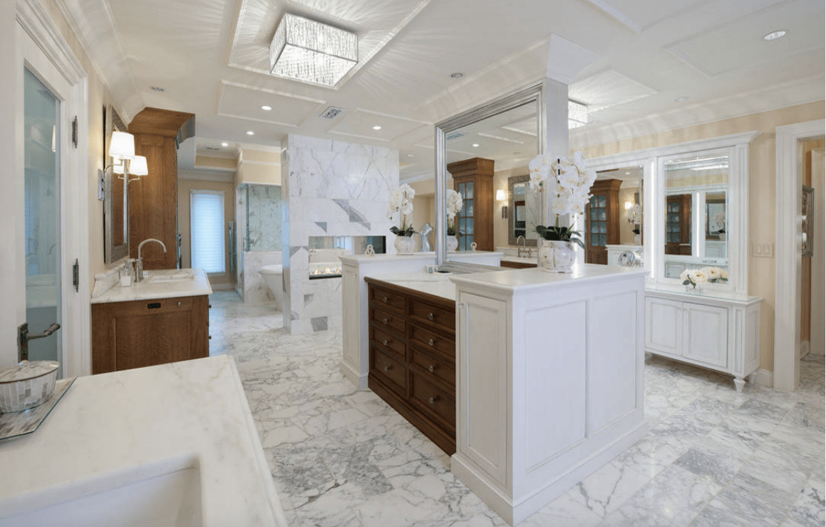Large primary bathroom featuring marble tiles flooring and a stylish white ceiling. There's a freestanding tub and a walk-in shower room.