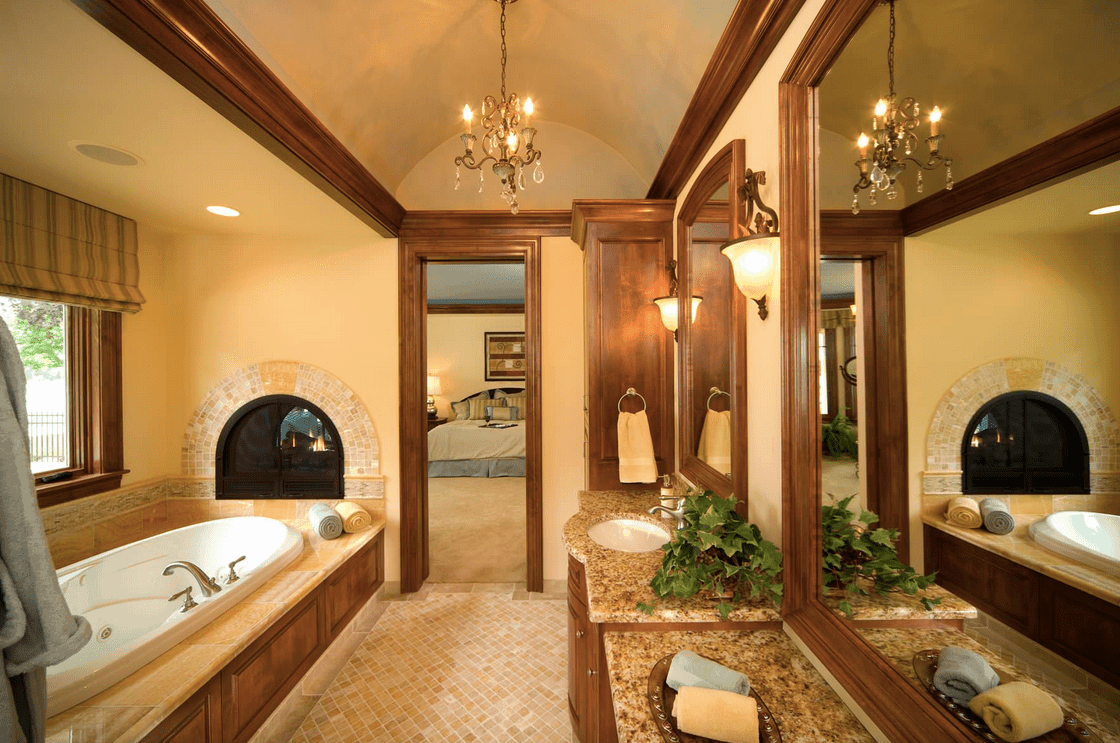 Primary bathroom with beige walls and a rustic shade. There's a bathtub set near the windows and has a fireplace at the edge.