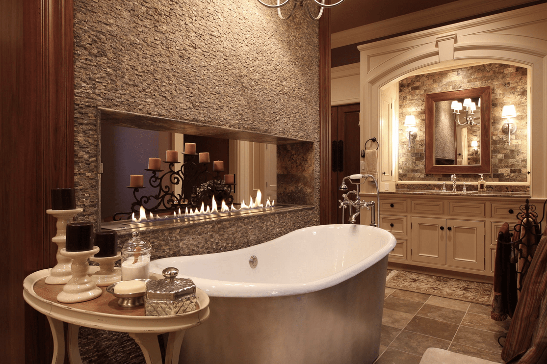 Primary bathroom with a stunning fireplace and a large freestanding tub set on the tiles flooring.