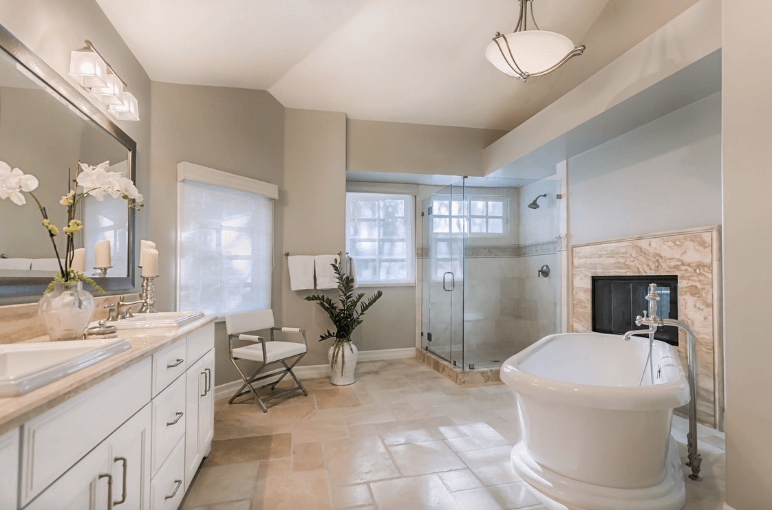 Spacious primary bathroom featuring a freestanding tub with a fireplace on the side, a walk-in shower room and a double sink.