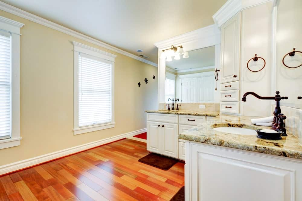 Spacious master bathroom featuring hardwood flooring and beige walls, along with marble countertops on the sink counters.