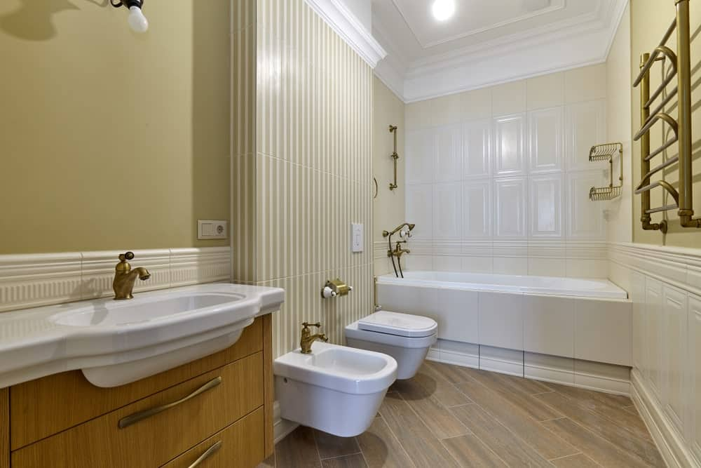 Master bathroom with a large bathtub and classy walls along with hardwood flooring and a fine white ceiling.