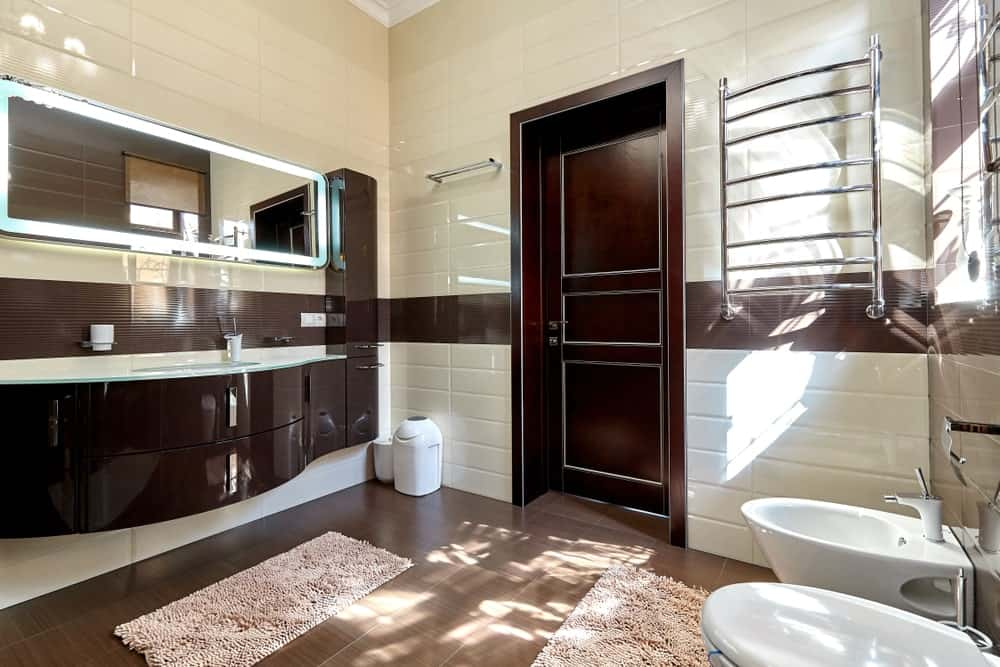 Master bathroom with a stunning floating vanity sink and hardwood flooring together with tiles walls and a tall ceiling.